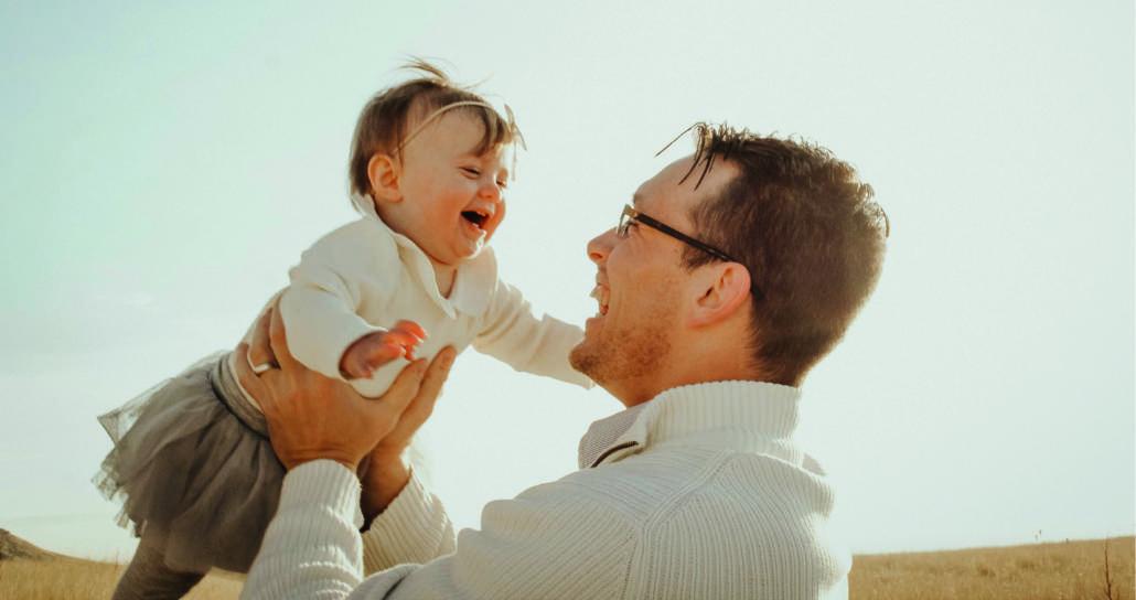 Vater hält lachendes Kind in den Armen.